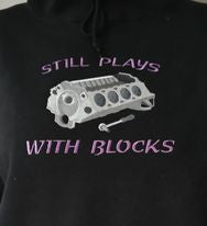 "An engine block on a black hoodie with saying ""still plays with blocks"""