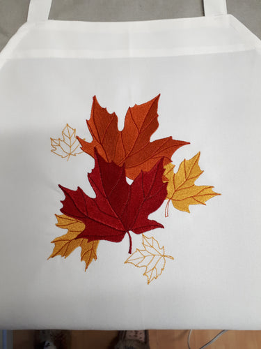 This white apron is stitched with 6 beautiful fall coloured maple leafs.  Four of the leaves ara a filled design, two are just outlines.  Colours are red, bronze and gold.