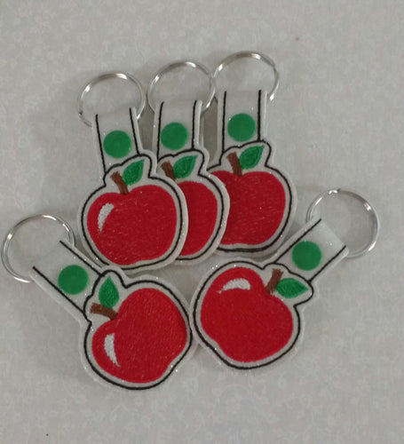 Red apples stitched on a white glitter vinyl with green leaves and a green snap tab