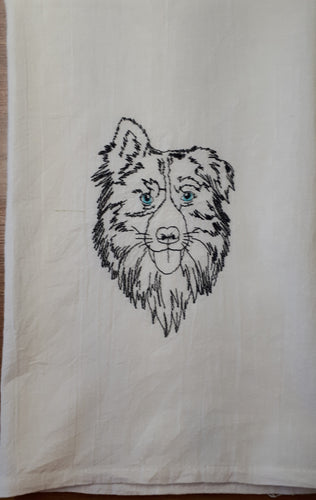 This is a flour sack towel with a sketch of an Australian shepherd stiched in black thread.  The eyes are a light blue.