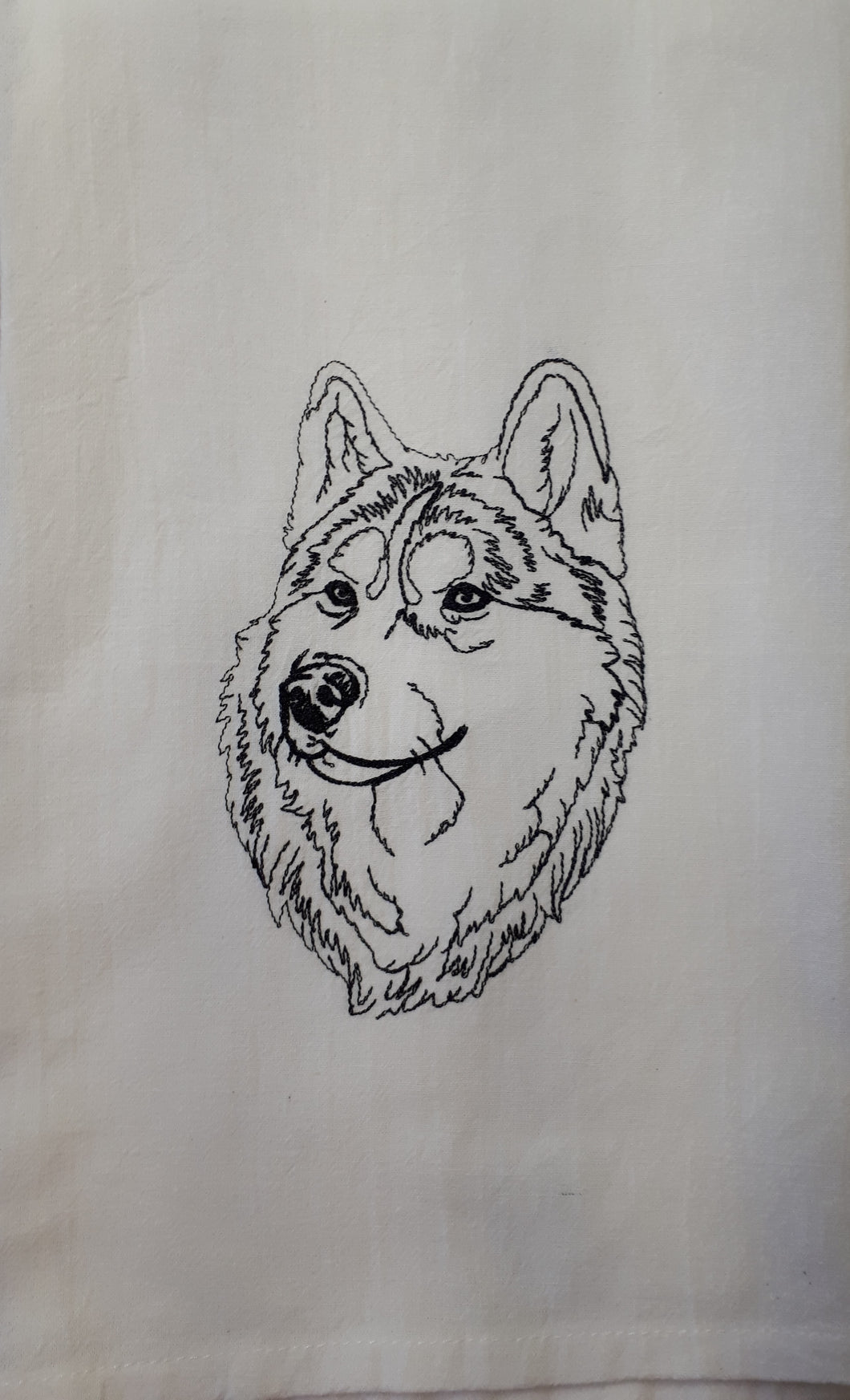 This white flour sack towel has a sketch of a husky stitched in black.