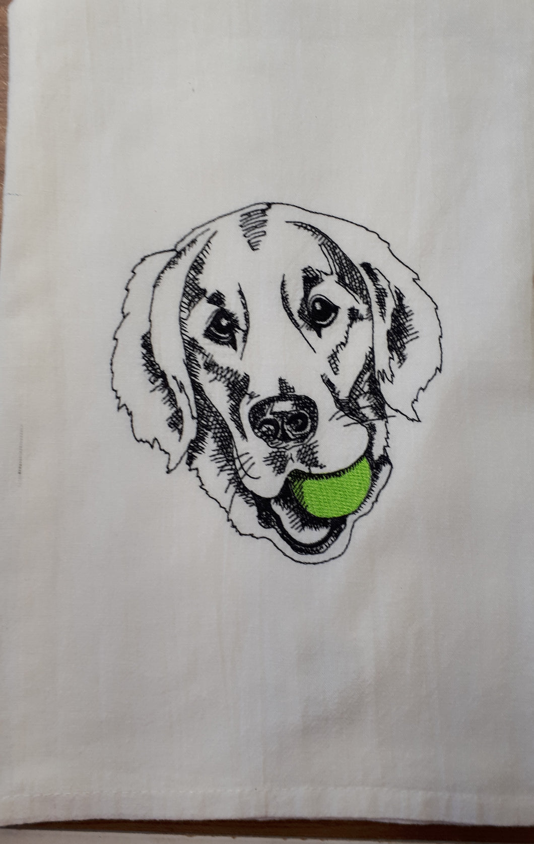 This white flour sack towel has a sketch of a golden retriever stitched in black thread with a green tennis ball in his mouth