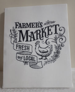 "This vintage farmers market design says ""farmer's market fresh and local"" in a charcoal thread on a white flour sack towel that was then stretched onto a canvas board to use a wall hanging.. The bottom of the design has a sketch of a chicken."