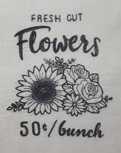"This vintage farmers market design says ""fresh cut flowers fifty cents per bunch"" in a charcoal thread on a white flour sack towel. The centre of the design is a sketch of a sunflower, two roses and a daisy."