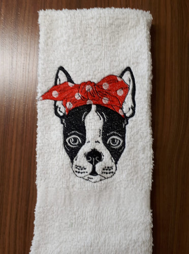 A Boston Terrier head stitched on a terry cloth hand towel.  Boston Terrier is wearing a red and white polka dot bow