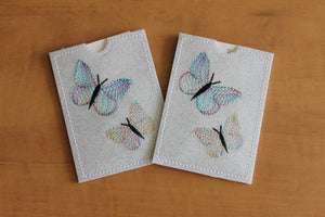 This gift card holder has Two dancing butterflies stitched in pastel variegated thread on  white glitter vinyl.
