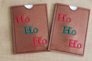 This gift card holder is made from bronze glitter vinyl stitched with the words HO HO HO that alternate in red thread, green thread, red thread.