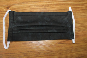 This is a pleated fabric face mask for personal portection against Covid-19. The fabric is a colourwash of black. The style shown is behind the ear elastic