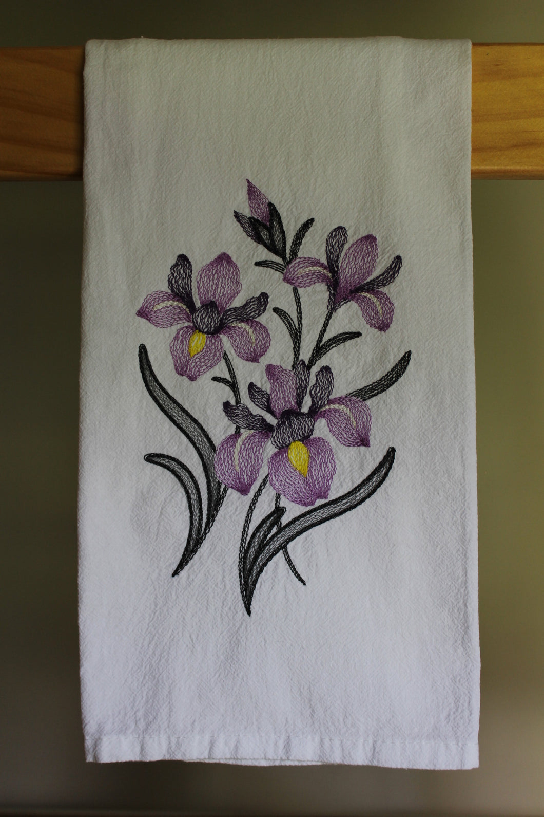 dark and light purple irises with yellow centres stitched in a sketch format with charchoal leaves and stems
