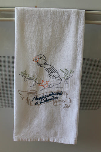 Stitched outline of a Puffin bird on rocks with a banner with the words Newfoundland & Labrador