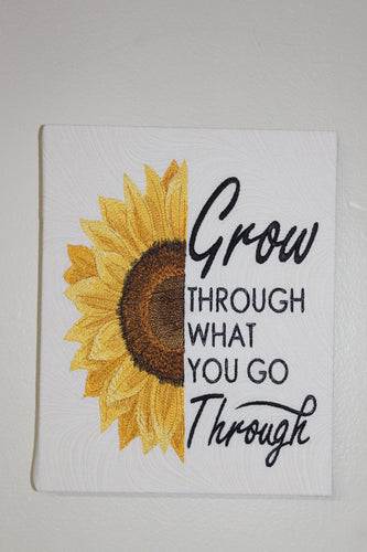Wall hanging of half a sunflower on the left side and the words