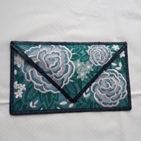An envelope clutch stitched on blue vinyl.  Design has large flowers in pink and smaller nosegay flowers in white.  Edges of clutch finished in a  navy satin type stitch.