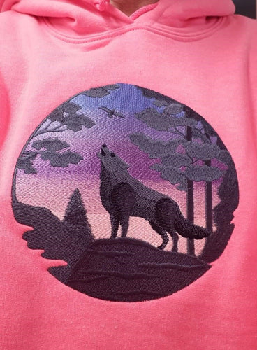 Black silhouette of a wolf howling with the sunset in the background.  Stitched on a pink hoodie.