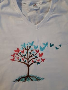 This t-shirt has a design of a tree in the grass with butterflies as leaves.  Some of the butterflies on the right are flying away like leaves in the wind.