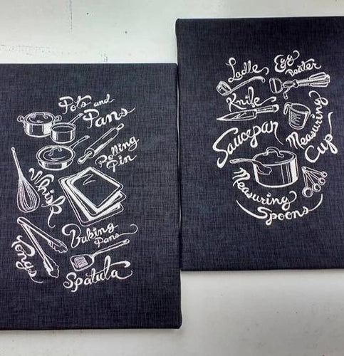Various kitchen utensils stitched out over two black canvas boards in silver thread.  The one on the left has Pots and pans, rolling pin, whisk, baking pans, tongs and spatula.  The one on the right has ladle, egg beater, knife, measuring cup, measuring spoons and saucepan
