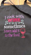 "Load image into Gallery viewer, This  picture depicts a black apron with the saying ""I cook with wine, sometimes I even add it to the food"" saying embroidered in various colours.  On the bottom right hand side of the design is an embroidered wine glass with wine in it."