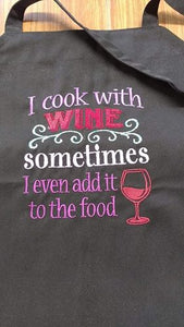 "This  picture depicts a black apron with the saying ""I cook with wine, sometimes I even add it to the food"" saying embroidered in various colours.  On the bottom right hand side of the design is an embroidered wine glass with wine in it."