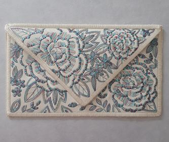 An envelope clutch stitched on cream vinyl. Design has large flowers and smaller nosegay flowers stited using blue/red/purple variegated thread. Edges of clutch finished in a cream satin type stitch.