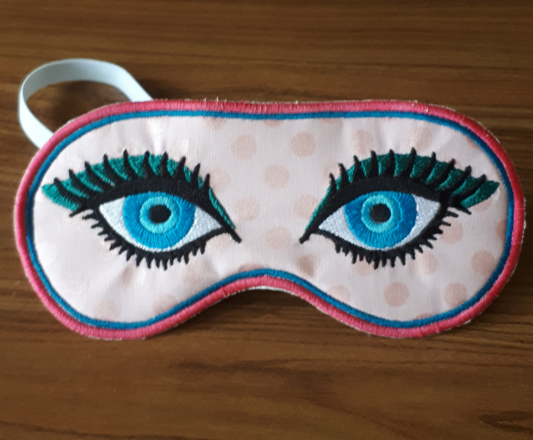 This sleep mask is made from shiny pink fabric.  The eyes stitched on the front are two shades of blue with a teal eye shadow and thick black eyelashes.  Mask has an inside row of satin stitching in blue and an outer row of satin stitching in dark pink.