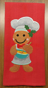 A ginderbread man wearing a chef hat and stirring a bowl of batter adorns this red waffle weave towel.
