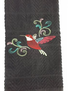 This sketch design of a hummingbird in flight with flourishes  is stitched on a black herringbone textured kitchen/bath towel.  The hummingbird is stitched with a red body, yellow throat and pink and blue wings.  The flourishes are made up of different colours.