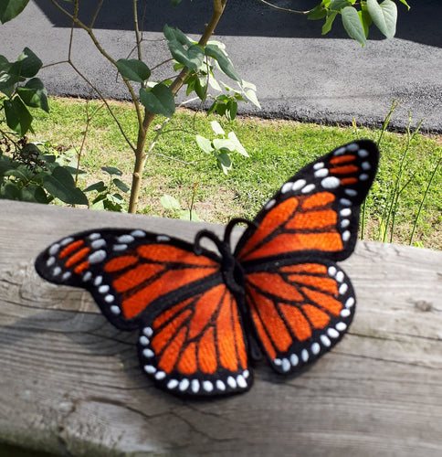 A beautiful three dimensional free standing lace monarch butterfly in orange black and white.  Butterfly is sitting on a  wooden hand rail.