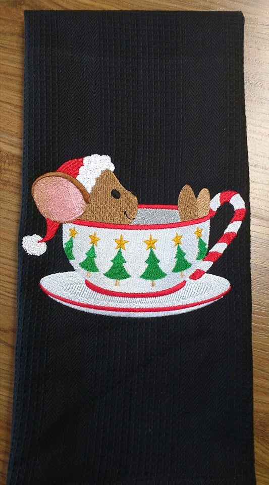 A black waffle weave towel stitched with a cute mouse in a tea cup.  The mouse is wearing a red santa hat.  The cup is white with a candy cane handle and green with gold star Christmas trees on cup.