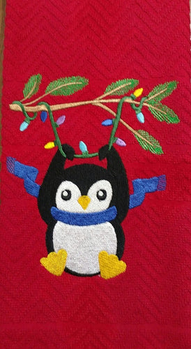 This red kitche/bath towel is embroided with a cute penguin hanging from Christmas Lights that are wrapped around an evergreen branch.  The black and white penguin has orange feet and beak and is wearing a blue scarf.
