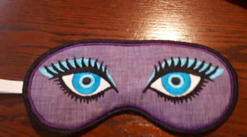 This sleep mask is made using a tone on tone purple fabric. The eyes stitched on the front are two shades of blue with a light blue eye shadow and thick black eyelashes. Mask has an inside row of satin stitching in purple and an outer row of satin stitching in black.