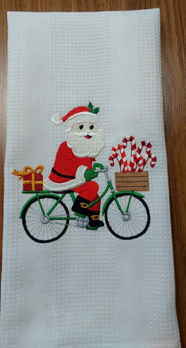 This white waffle weave towel is embroidered with Santa riding a green bicycle.  A basket full of candy canes and a red gift with a gold bow on the back.