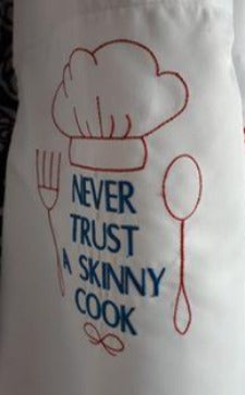 This white apron is stitched with the saying