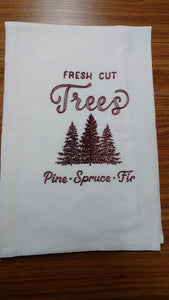 "This vintage Christmas design says ""fresh cut trees, pine, spruce, fir."" stitched with red thread on a white flour sack towel.  In the centre of the design are 3 evergreen trees."