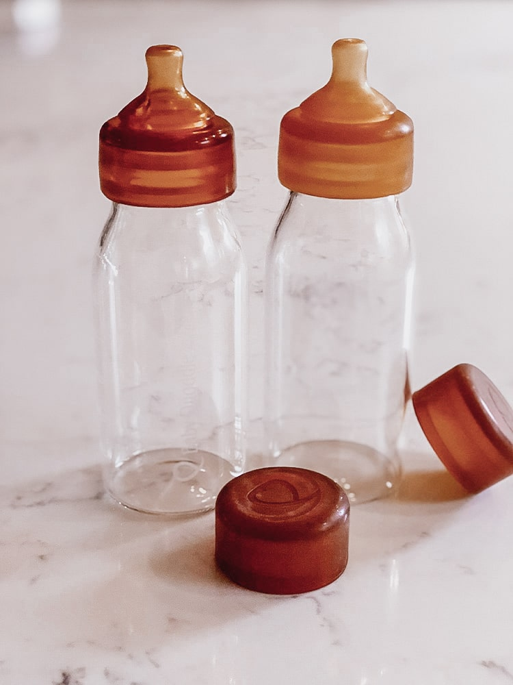 Picture of two glass bottles side by side with rubber teats and lids