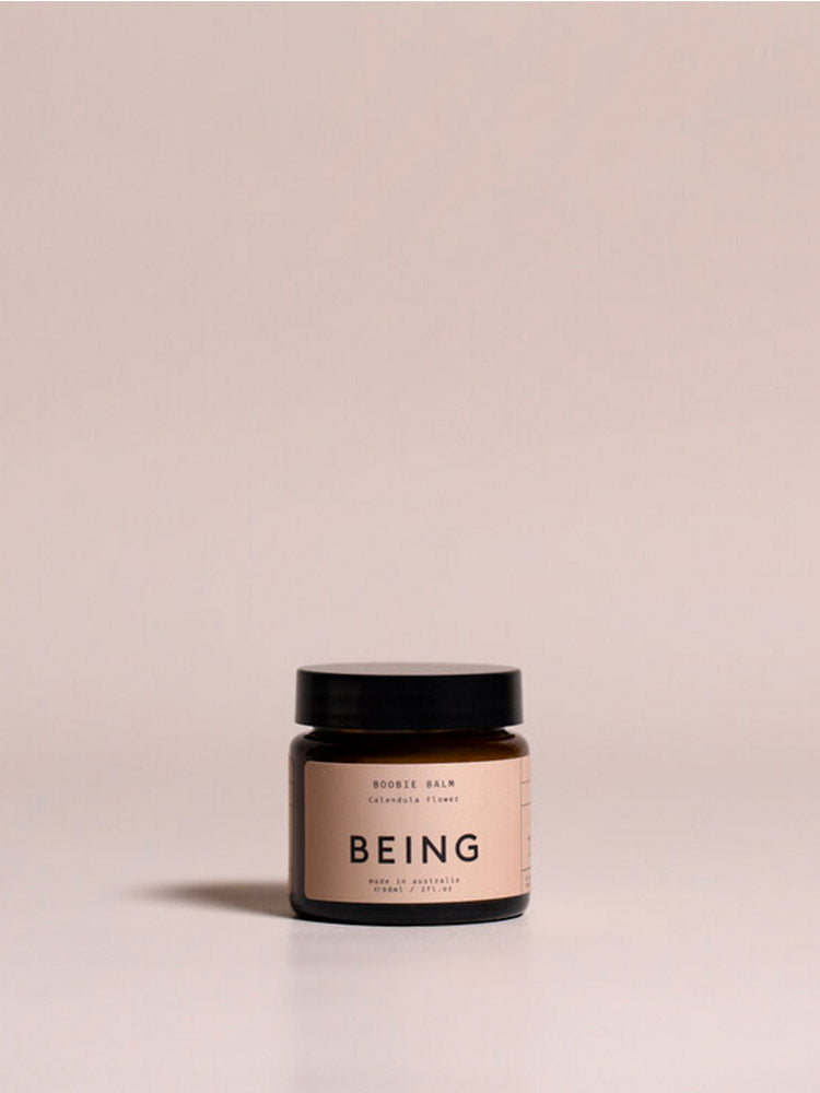 Jar of Being Skincare Boobie Balm against a pink background