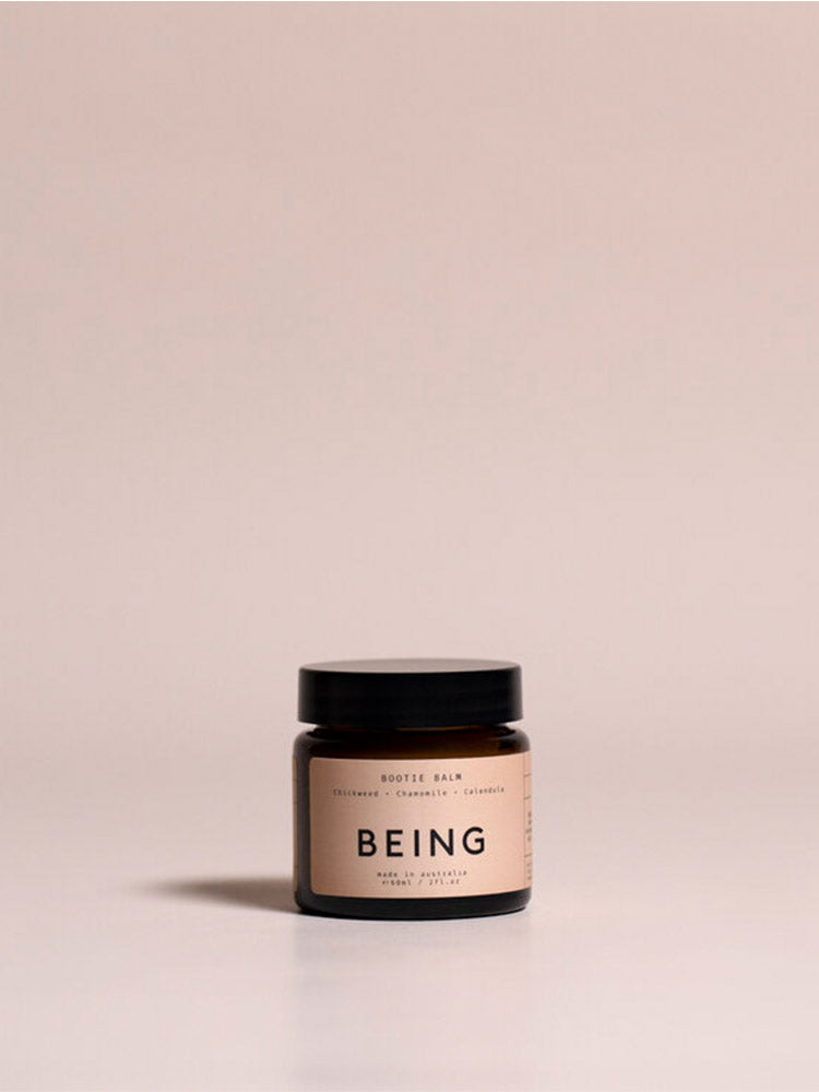 Jar of Being Skincare Bootie Balm against a pink background
