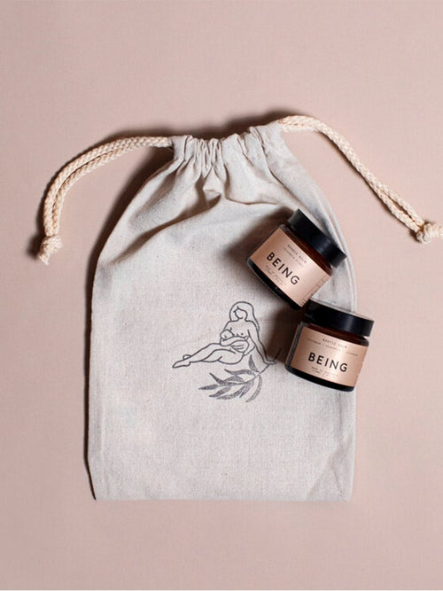 Drawstring calico pouch and 2 jars of Being Skincare balm with pink labels
