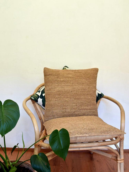 Two sustainable raffia cushions on rattan chair