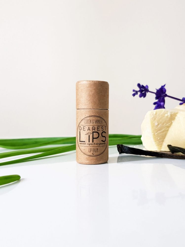 a tube of eco friendly lip balm surrounded by foliage and shae butter