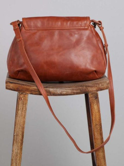 Brown leather bag back view sitting on stool