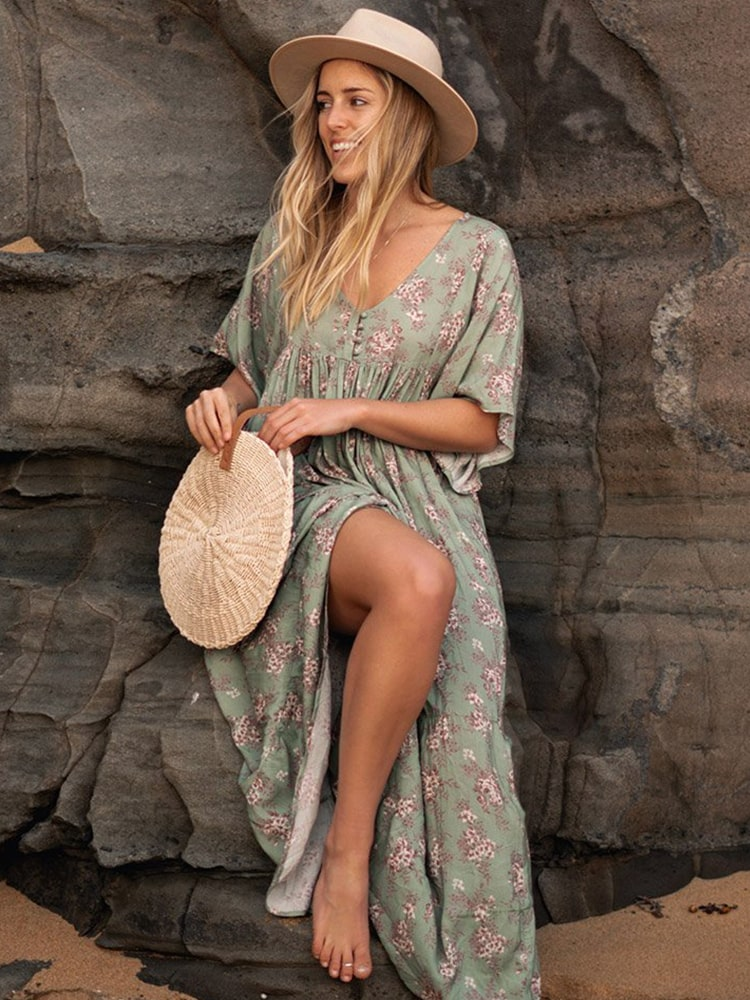 Lady standing against rock in long sage green floral dress