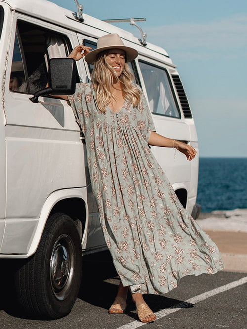 Lady standing against Van in long sage green floral dress
