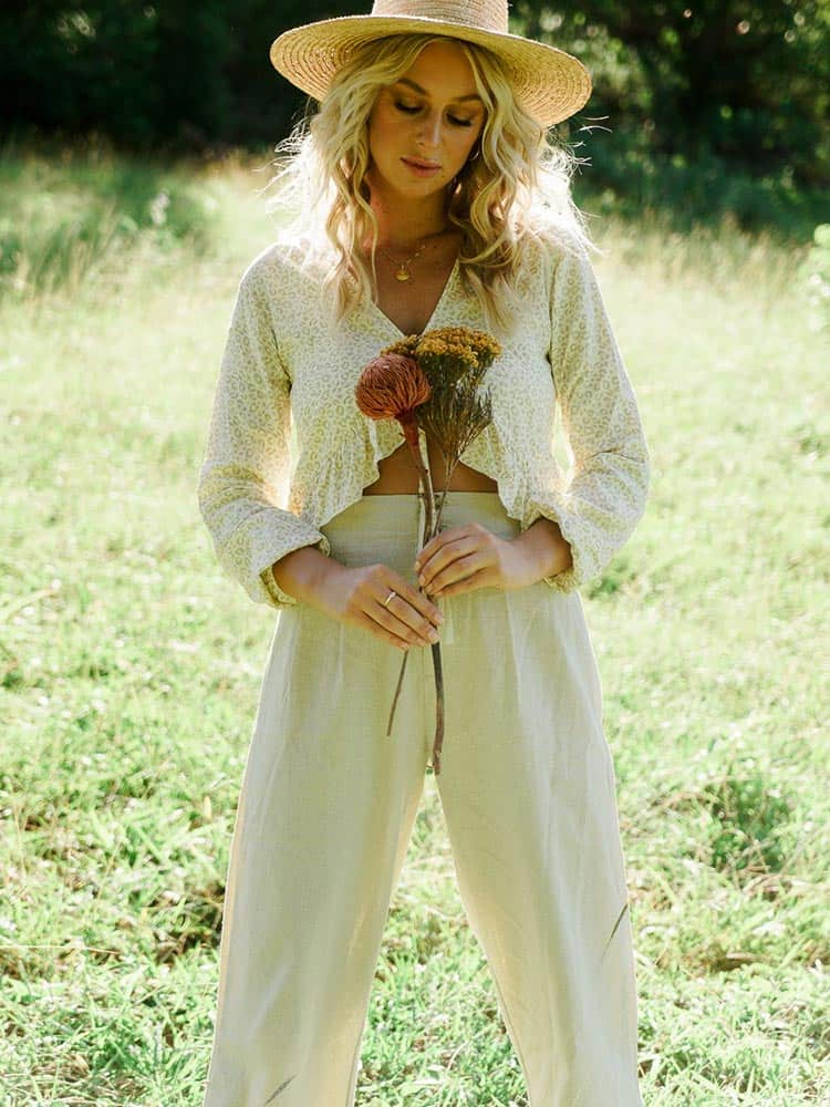 Young woman holding flowers in a field wearing natural linen pants