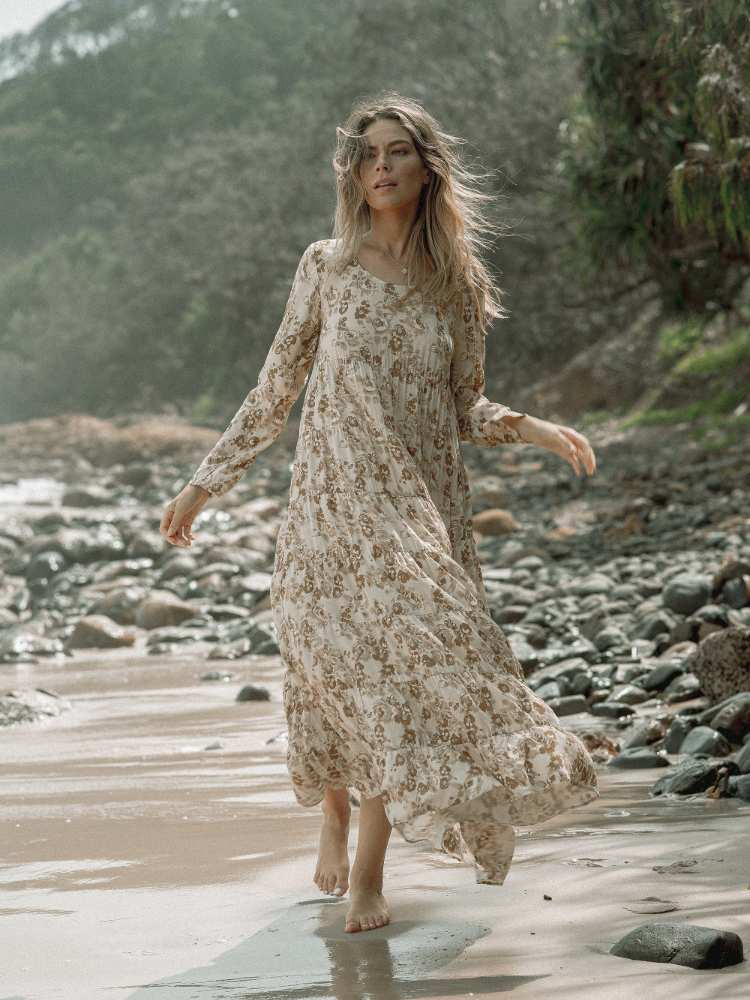 Girl walking on beach with long dress and bare feet