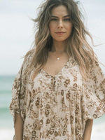 Close up of girl with long hair blowing in the wind at the beach with floral boho dress on