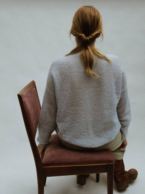 Lady sitting on a chair in Feather Knit from Francie Melbourne showing the back of the jumper in Eggshell blue