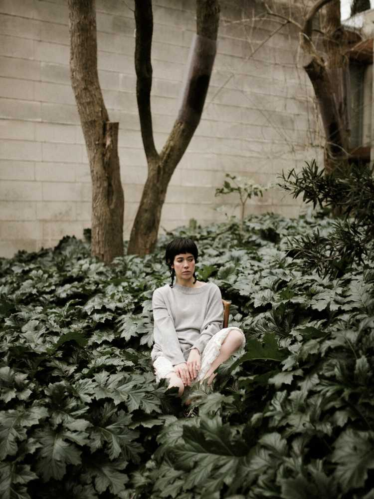 Lady sitting in Plants wearing Francie dew cotton knit