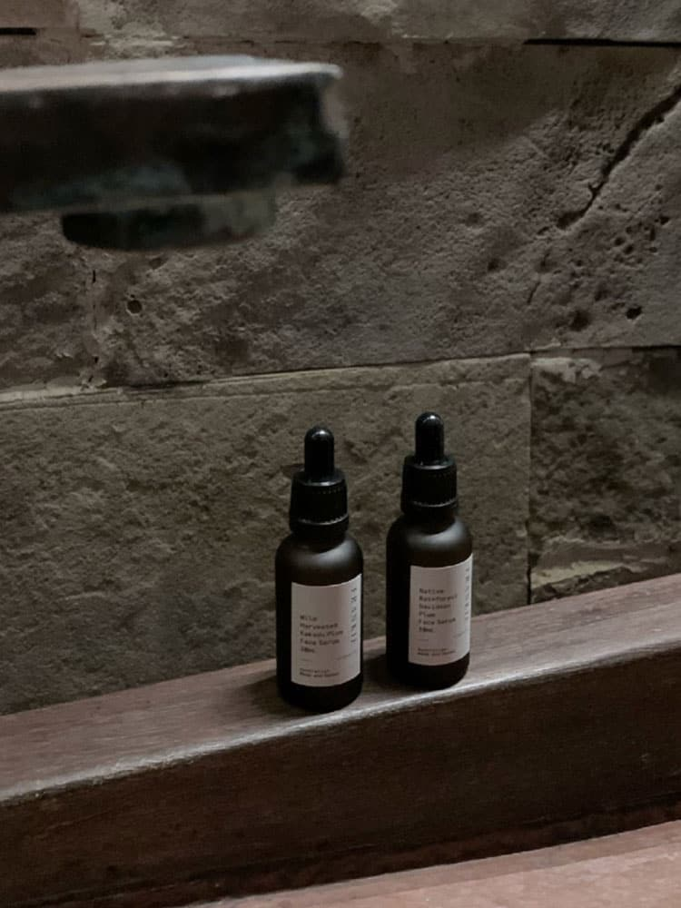 Frankie Organics AM to PM Face Serum Duo against stone bathroom wall