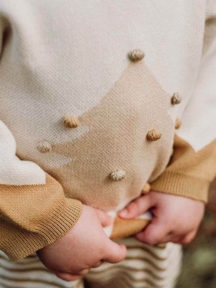 Close up of child's hands holding Christmas knit