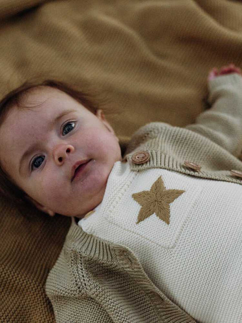 Baby lying down wearing a cream onesie with  Christmas star detali