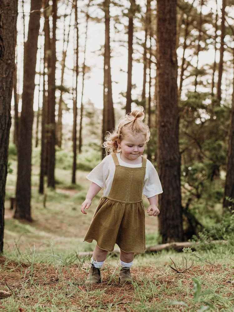 Little girl walking through the forest